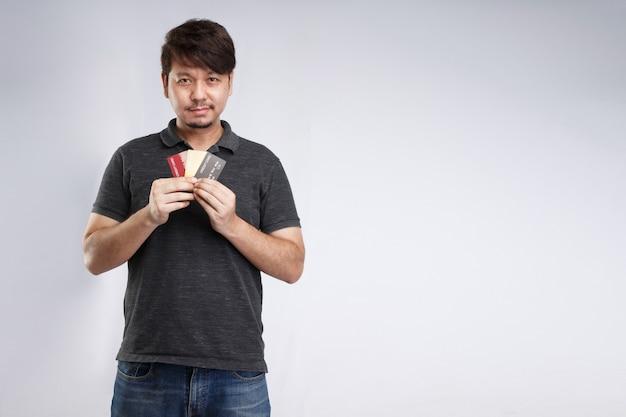 Homem asiático sorridente segurando três cartões de crédito