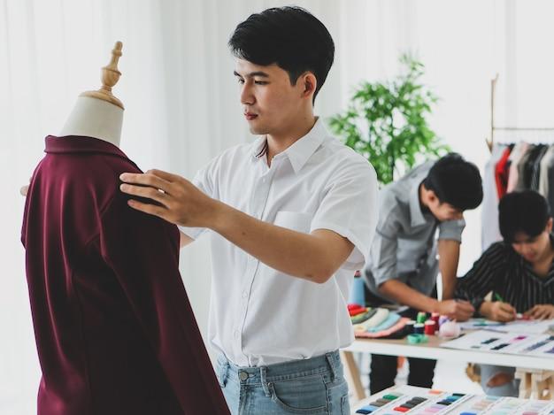 Homem asiático sorrindo com felicidade e autoconfiança enquanto mede roupas da moda em um manequim perto de colegas durante o trabalho em uma oficina de alfaiate