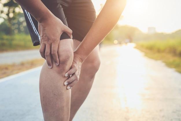 Homem asiático tem de joelhos enquanto corre na estrada no parque