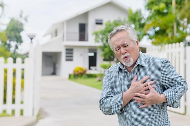 Homem asiático tendo um ataque cardíaco doloroso no peito em um parque residencial ao ar livre - conceito de doença cardíaca