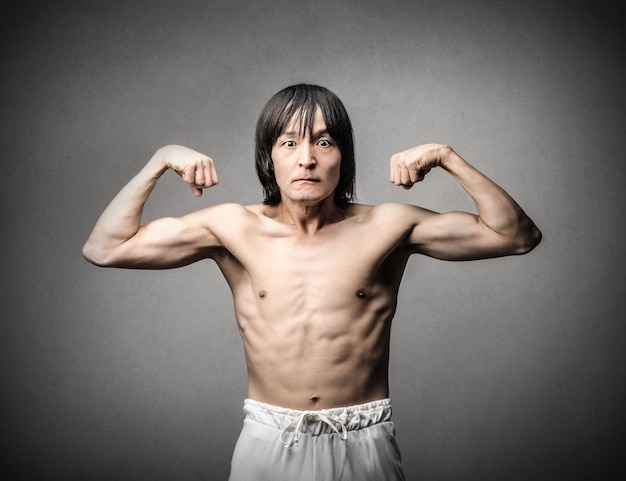 Homem asiático tentando parecer forte