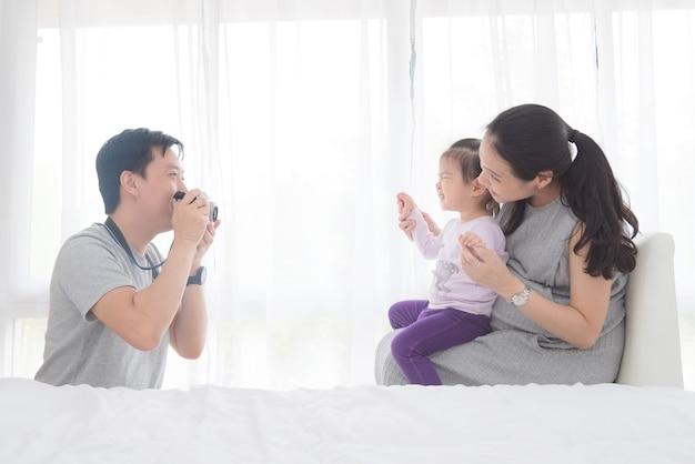 Homem asiático tirando foto sua esposa e filha pela câmera em casa