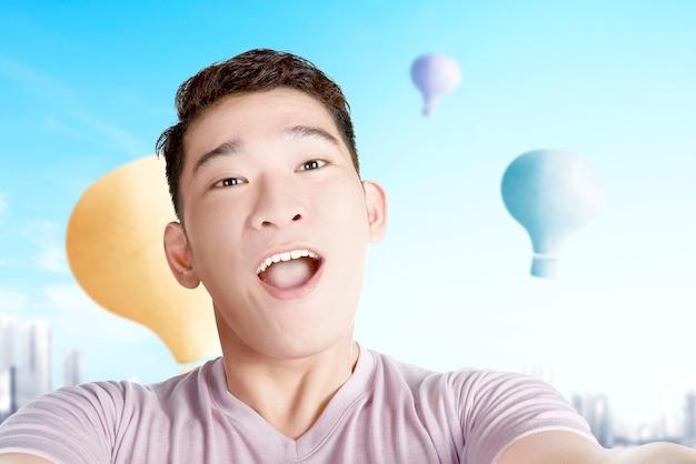 Homem asiático tirando uma selfie com um balão de ar colorido voando com o fundo da cidade