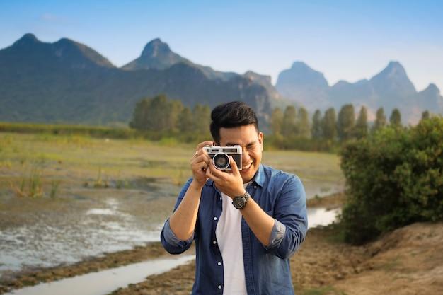 Homem asiático tirar foto com camara
