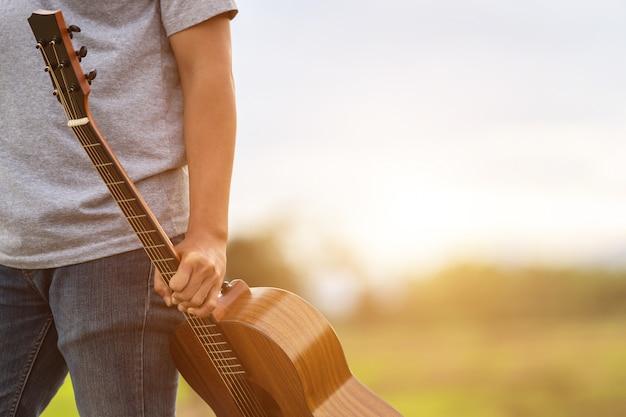 Homem asiático tocando guitarra no campo de arroz verde na hora do sol