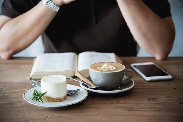 Homem asiático, tomando um café e lendo um livro