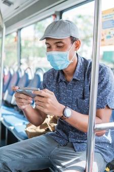 Homem asiático torcendo e jogando em seu celular enquanto anda no transporte público