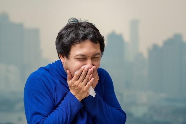 Homem asiático, tossir, com, tecido, contra, ar, poluição, com, em, a, sacada, de, alto, apartamento