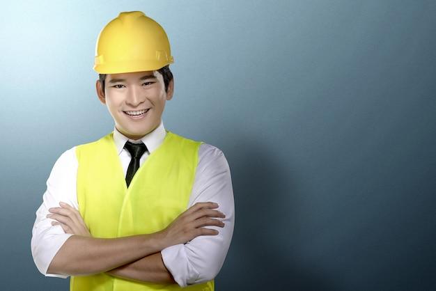 Homem asiático trabalhador com pé de capacete amarelo
