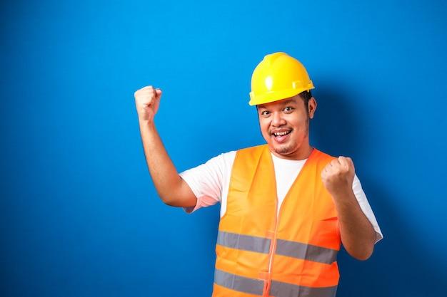 Homem asiático trabalhador usando capacete de segurança está feliz celebrando sua vitória cerrando os punhos