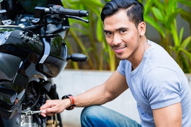 Homem asiático trabalhando em sua scooter olhando para a câmera