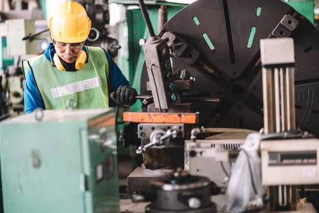 Homem asiático trabalhando em uma fábrica com capacete amarelo