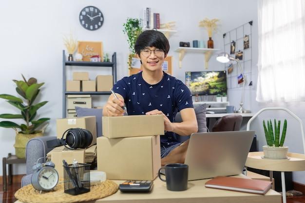 Homem asiático trabalhando para vender on-line, escrevendo o endereço de um pacote de pedidos