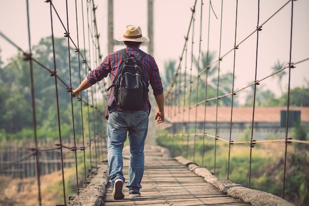 Homem asiático turista andando na ponte de madeira velha e quebrada
