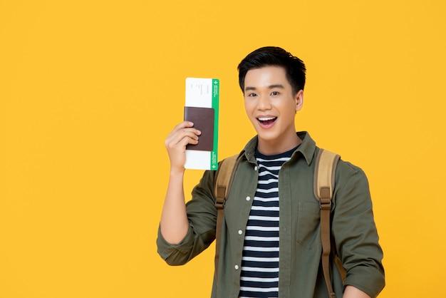 Homem asiático turista sorrindo e segurando o passaporte com cartão de embarque