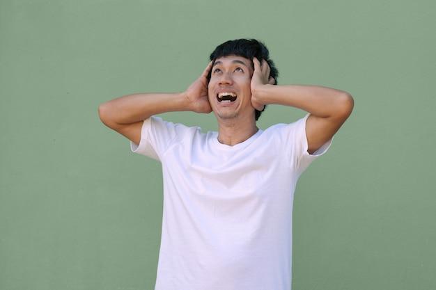 Homem asiático usa camiseta branca olhando vista de cima com cara de choque surpresa. imagem isolada do trajeto de grampeamento. imagem para promoção e apresentação.