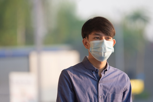 Homem asiático usa máscara facial para proteger o coronavírus covid 19