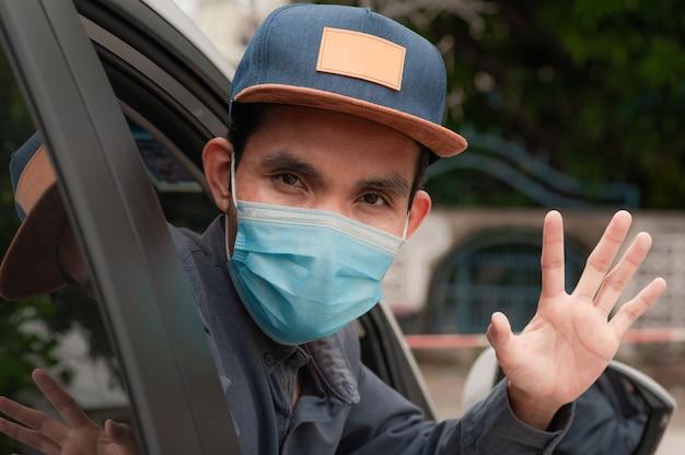 Homem asiático usa máscara no carro