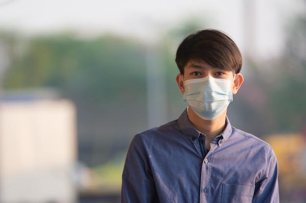 Homem asiático usa máscara para proteger o coronavírus covid 19 em pé ao ar livre na rua urbana