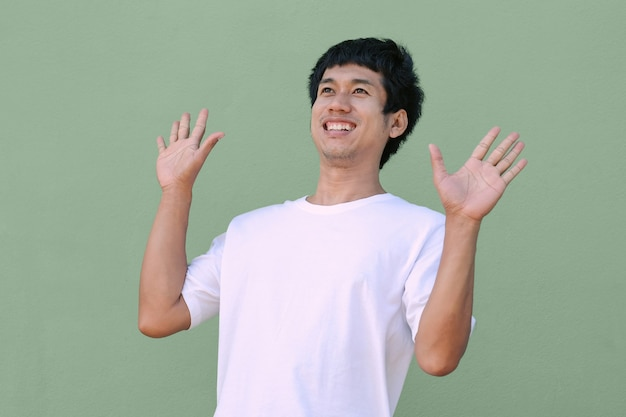 Homem asiático usa um sorriso de camiseta branca, olhando a vista de cima com uma cara feliz. imagem isolada do trajeto de grampeamento. imagem para promoção e apresentação.