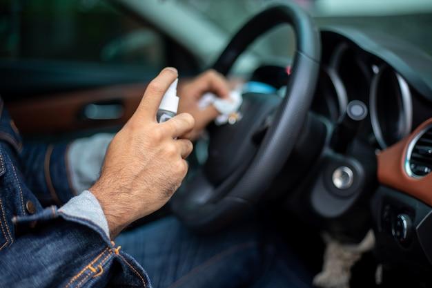 Homem asiático usando álcool spray para limpar o carro para proteção contra coronavírus