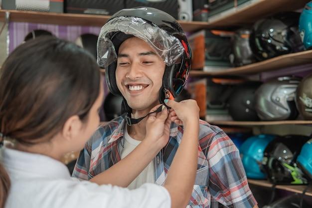 Homem asiático usando capacete com a ajuda de um vendedor de capacete no fundo da prateleira de exposição
