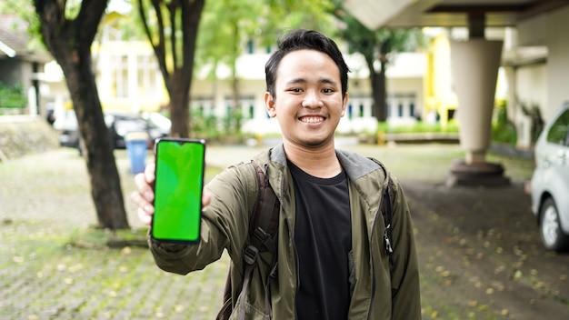 Homem asiático usando celular com tela verde