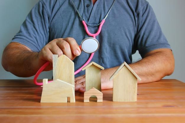 Homem asiático usando estetoscópio, verificando o modelo de madeira da casa em piso de madeira