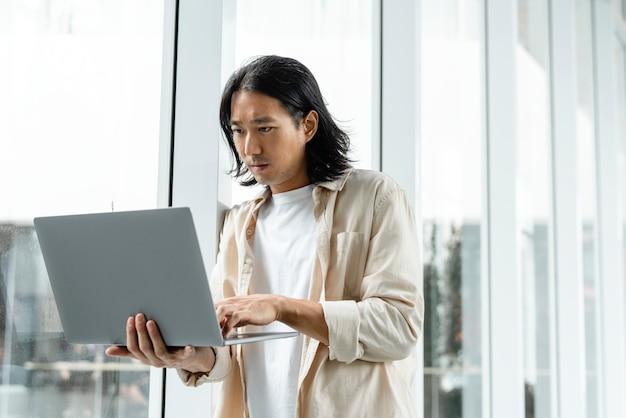 Homem asiático usando laptop enquanto anda pela cidade