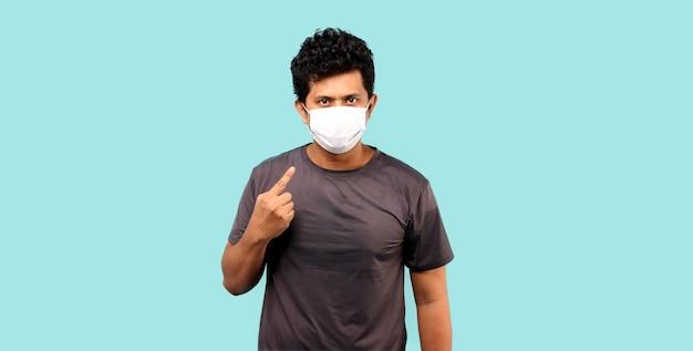 Homem asiático usando máscara, apontando o dedo isolado na parede azul claro