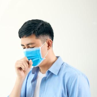 Homem asiático usando máscara cirúrgica, tossindo na estação de metrô com passagem de pessoas lotadas. prevenção de surto de coronavírus wuhan (covid-19)