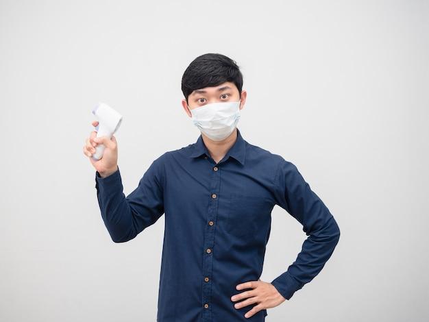 Homem asiático usando máscara e segurando o medidor infravermelho para digitalizar o fundo branco do retrato