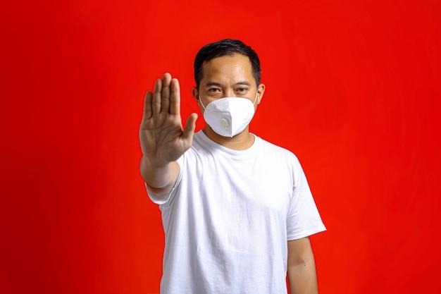 Homem asiático usando máscara médica e gesticulando para parar em um fundo vermelho