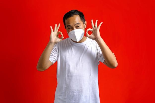 Homem asiático usando máscara médica gesticulando ok com as duas mãos em um fundo vermelho