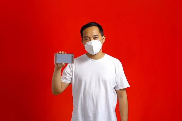Homem asiático usando máscara médica mostrando telefone inteligente com tela em branco sobre fundo vermelho