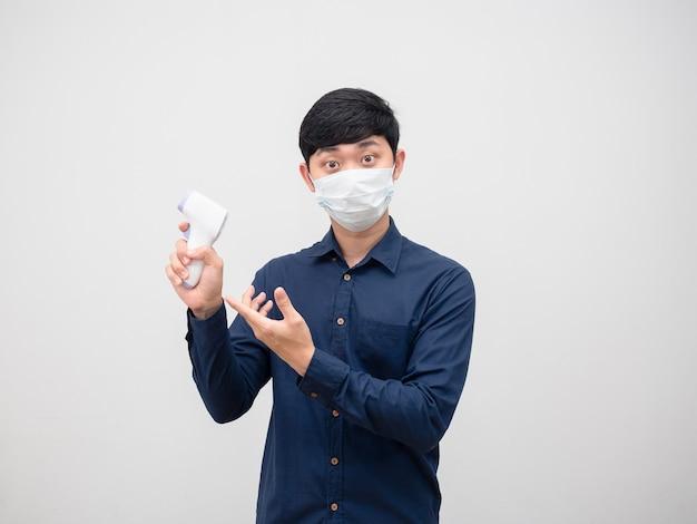 Homem asiático usando máscara sugere temômetro infravermelho na mão para digitalizar o fundo branco do retrato