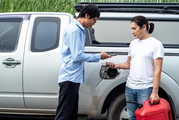 Homem asiático usando o aplicativo no celular para pagar pelo produto que é óleo de carro