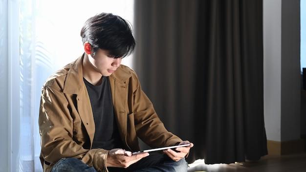 Homem asiático usando tablet digital e sentado no chão de madeira em casa.