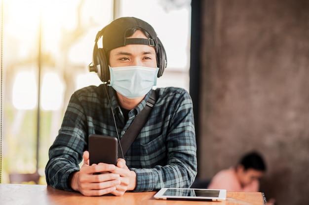 Homem asiático, usar telefone móvel, em, café, indoor, desgastar, um, máscara facial, proteger, corona, vírus, novo, normal, estilo vida