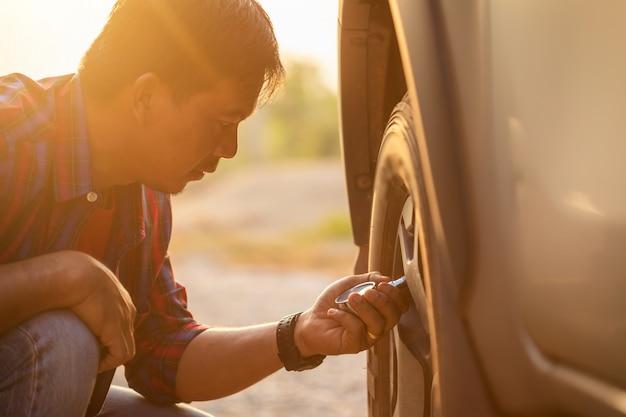 Homem asiático, verificando a pressão do ar do seu carro