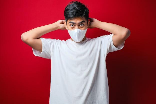 Homem asiático vestindo camiseta branca e colocando uma máscara facial com uma das mãos colocando o elástico em uma orelha sobre um fundo vermelho