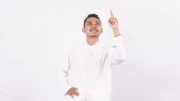 Homem asiático vestindo roupas muçulmanas e apontando para um espaço em branco isolado na tela