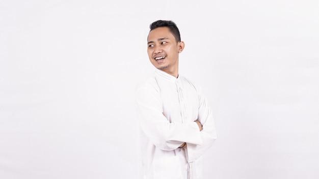 Homem asiático vestindo roupas muçulmanas e apontando para um espaço em branco isolado na tela Foto Premium