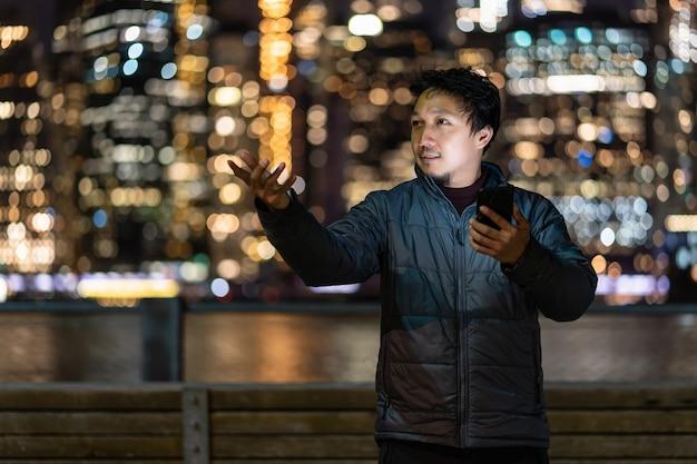 Homem asiático vestindo um sobretudo usando um telefone celular inteligente com ação de sorriso