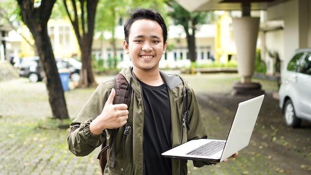 Homem asiático vestindo uma bolsa enquanto segura um laptop com gesto de ok