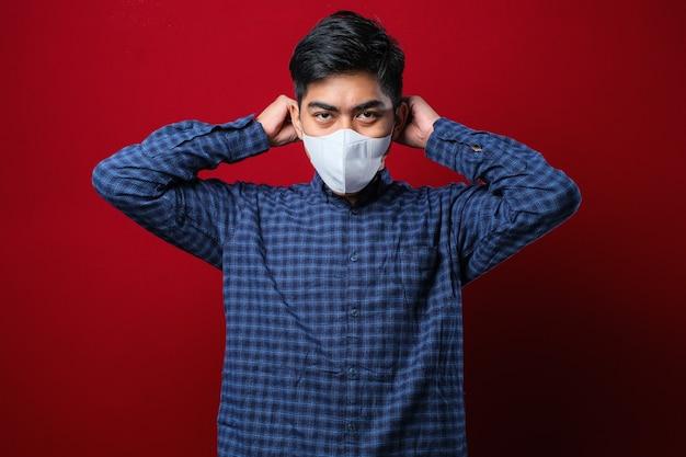 Homem asiático vestindo uma camisa casual e colocando uma máscara facial com uma das mãos colocando o elástico em uma orelha sobre um fundo vermelho