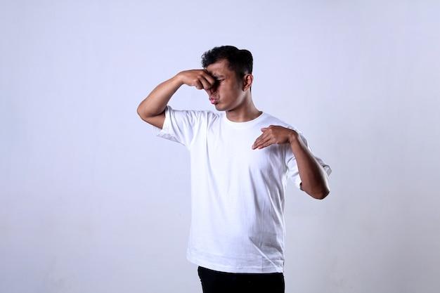 Homem asiático vestindo uma camiseta branca com uma expressão de cheirar mal cheiroso e cobrindo o nariz