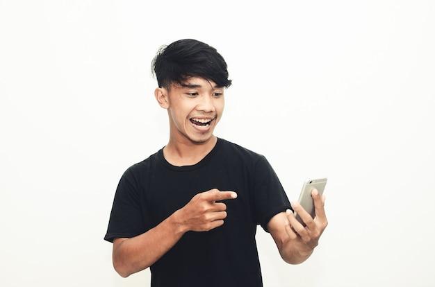 Homem asiático vestindo uma camiseta preta casual com uma expressão de choque ao ver seu telefone