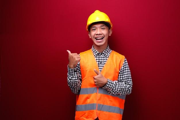 Homem asiático vestindo uniforme de contratado e capacete de segurança apontando e aparecendo com o polegar para cima