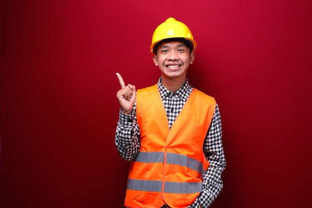 Homem asiático vestindo uniforme de contratado e capacete de segurança apontando para o espaço vazio
